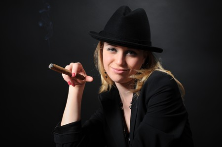 Portrait of a beautiful girl in a hat with a cigar on a black background photo