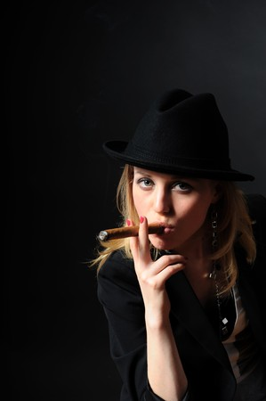 Beautiful girl in a hat with a cigar on a black background looks into the camera photo