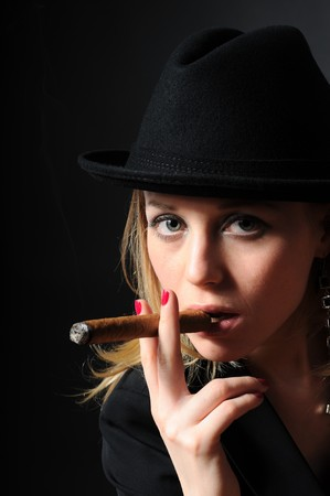 Beautiful girl in a hat smoking a cigar on a black background looks into the camera Stock Photo - 6883104