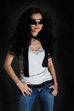 Girl in a white shirt and jeans on a black background photo