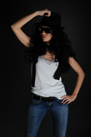 Portrait of a girl in a white T-shirt, hat and sunglasses on a black background photo