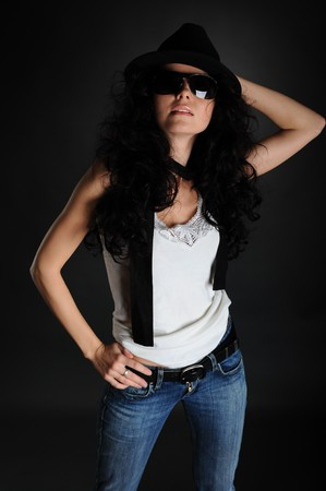 Girl in a white T-shirt, hat and sunglasses on a black background photo