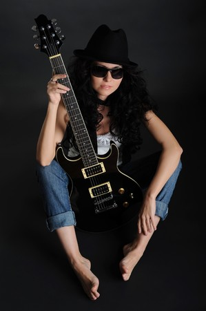 Girl in a hat and sunglasses sitting on the floor with a guitar in his hands photo