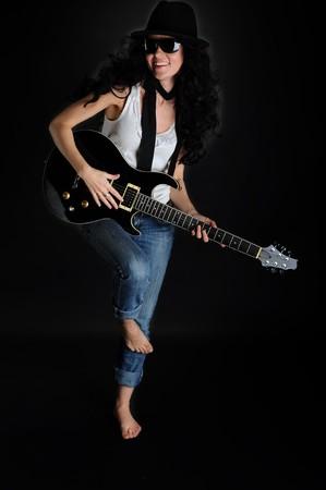 Retrato de una hermosa muchacha sonriente con una guitarra en sus manos sobre un fondo negro  Foto de archivo - 6883117