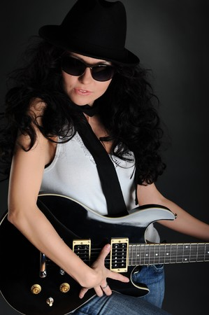 Portrait of a girl in a hat with a black guitar in his hands photo