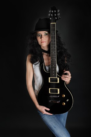 Portrait of a beautiful long-haired girl with a guitar in his hands on a black background photo