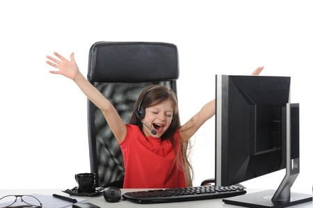 Joyful girl in the office in front of computer. Isolated on white background photo