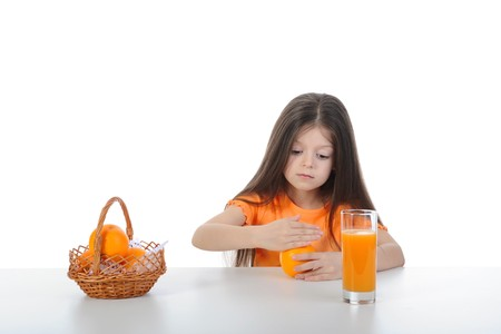 Girl with orange in their hands at the table. Isolated on white background photo
