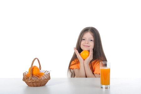 Girl with an orange at the table. Isolated on white background photo