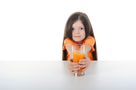 Girl with orange juice at the table. Isolated on white background photo