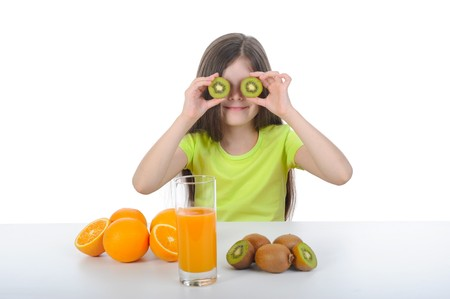 Girl shows kiwi slices sitting at the table. Isolated on white background photo