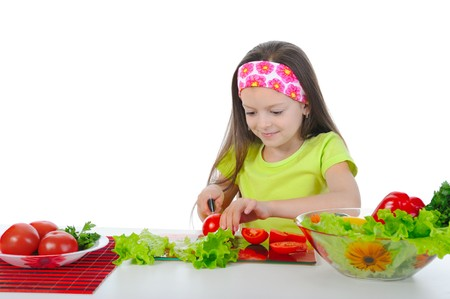 little girl is preparing salad at the table. Isolated on white background photo