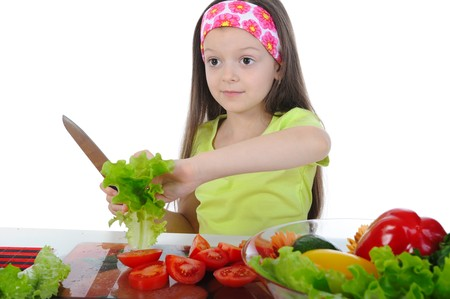 Little girl cut salad at the table. Isolated on white background photo