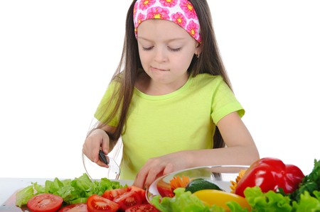 Little girl cut tomatoes at the table. Isolated on white background photo