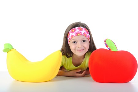 little girl at the table with a big banana and apple. Isolated on white background photo