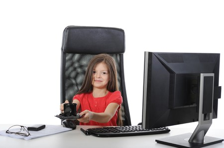 little girl with a cup of coffee at a table in front of a computer. Isolated on white background photo