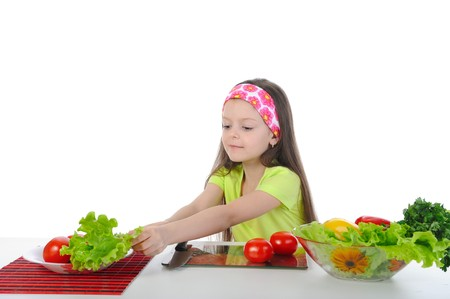 Little girl preparing breakfast table. Isolated on white background photo