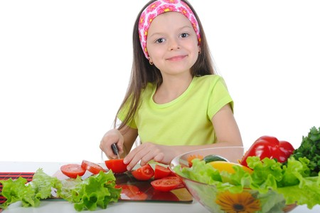 little girl cut fresh vegetables. Isolated on white background photo