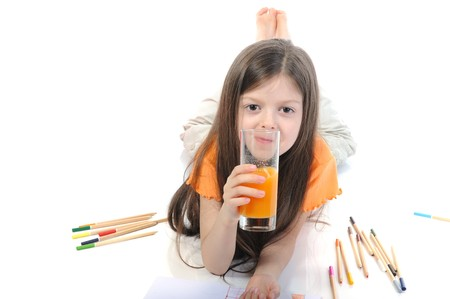 Little girl drinking juice from a glass lying on the floor. Isolated on white background photo
