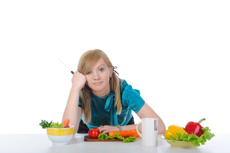 beautiful young girl on the kitchen table. Isolated on white background. carrots photo