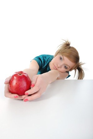 Young beautiful girl with a red apple on the table. Isolated on white background. photo