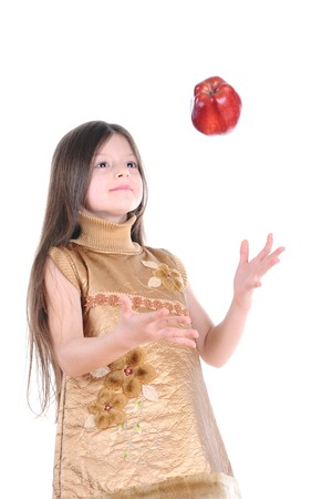 little girl in a gold dress catches a big red apple. Isolated on white background photo