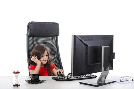 little girl looks in the monitor at the table in front of a computer. Isolated on white background photo