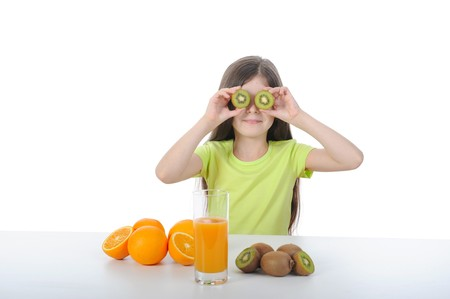 Little girl holding kiwi slices in front of his eyes. Isolated on white background photo
