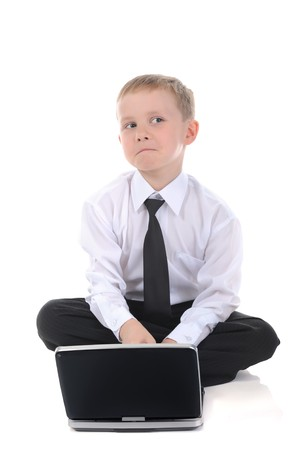 Little businessman with a laptop sitting on the floor. Isolated on white background photo