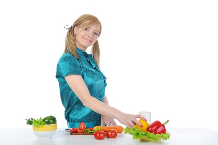 Young housewife prepares a salad of fresh vegetables. Isolated on white background photo