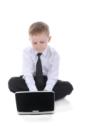Boy in business clothes sitting on the floor with a laptop. Isolated on white background photo