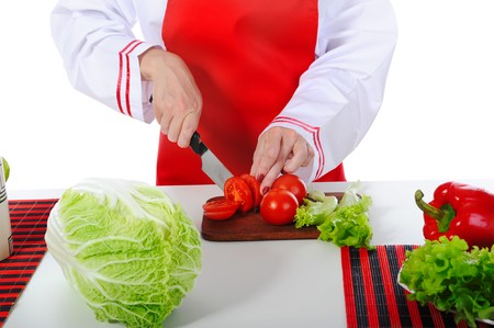 chef cut the tomatoes in the kitchen. Isolated on white background Stock Photo - 6970615