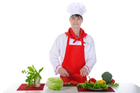 Chef in uniform cut tomatoes. Isolated on white background photo