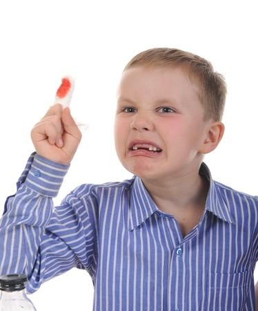 Crying boy with a bandaged finger. Isolated on white background photo