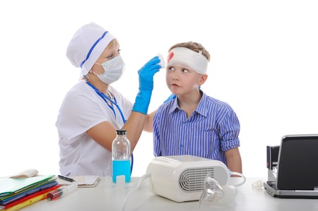 Doctor bandaged the boys head. Isolated on white background photo