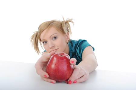beautiful young girl with an apple on the table. Isolated on white background photo
