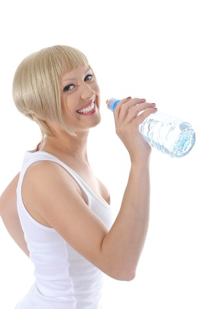 Young beautiful blonde drinking water from a bottle. Isolated on white background photo