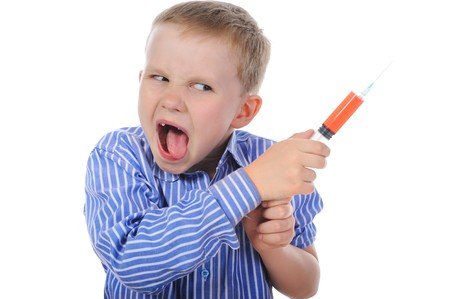 Portrait of a young boy with a syringe in his hand. Isolated on white background photo