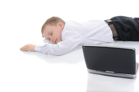 little boy fell asleep in front of a laptop. Isolated on white background Stock Photo - 6971320
