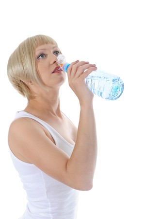 Sports girl drinks water from a bottle. Isolated on white background photo