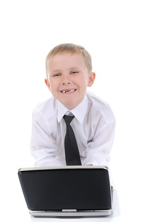 Happy little boy with a laptop. Isolated on white background photo