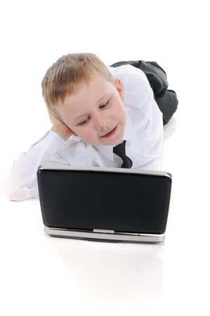 Little boy lying on the floor with a laptop. Isolated on white background Stock Photo - 7013857