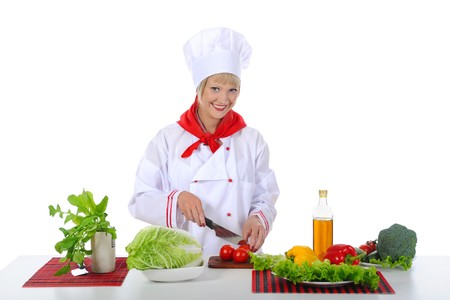young girl cuts tomatoes. Isolated on white background photo