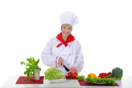 young girl cuts the tomatoes in the kitchen. Isolated on white background Stock Photo - 7013879