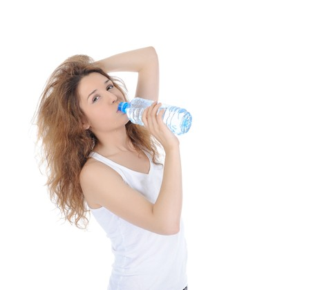 brune: Charming brunette drinking water from a bottle. Isolated on white background Stock Photo