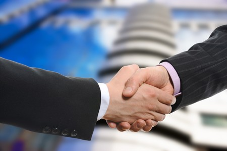 Handshake of two men in black suits on the background of the business building