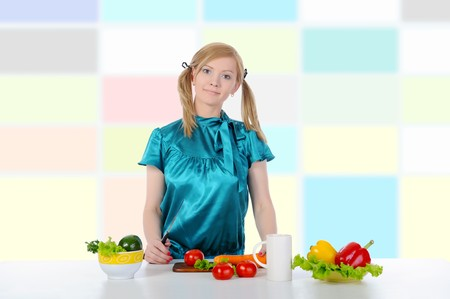 Beautiful girl in the kitchen preparing a salad photo