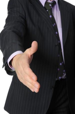 buen trato: Hombre de negocios en un traje sostiene su mano para un apret�n de manos. Aislados en fondo blanco