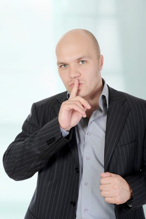 young businessman holding a finger to his mouth. Stock Photo - 7296667
