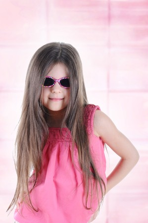 Portrait of a beautiful little long-haired brunette in sunglasses.  photo